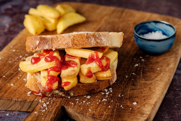 """A staple of the english diet a """"Chip Butty"""". Potato fries between two slices of buttered white bread, with tomato ketchup! A snack, a meal, a hangover cure, you decide! Delicious. Colour, horizontal with some copy space."""