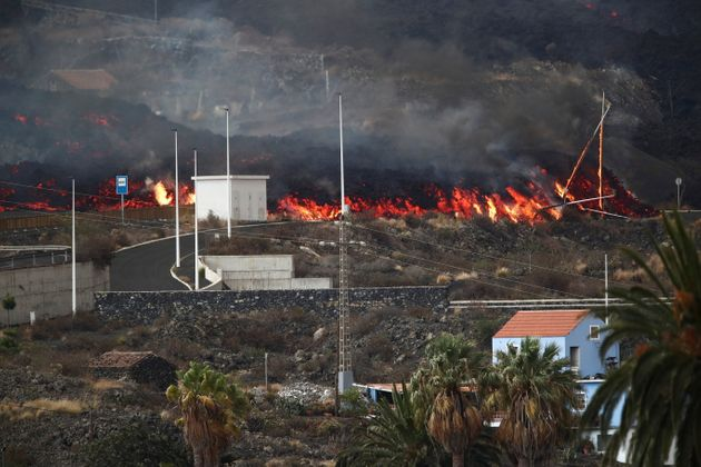 Lava rolls down behind street light posts in Los Llanos as the Cumbre Vieja volcano continues to erupt...