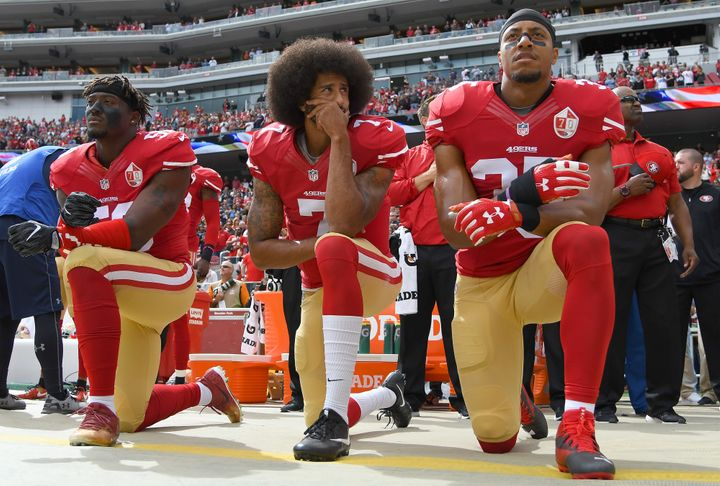 Eli Harold, Colin Kaepernick and Eric Reid of the San Francisco 49ers kneel on the sideline during the national anthem at a game in 2016.