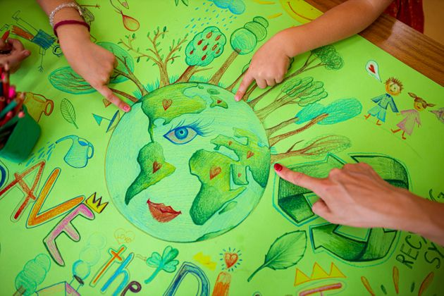 Caring female preschool teacher together with her female student, drawing the poster for the Eart Day,...