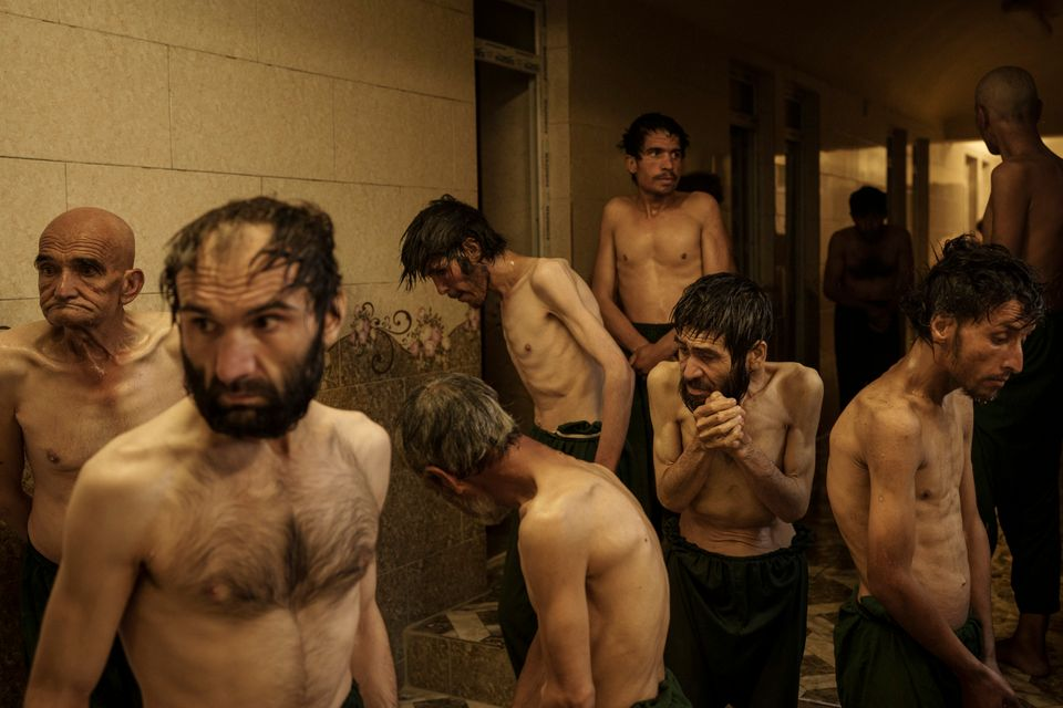 Drug users detained during a Taliban raid wait to be shaved after arriving at Avicenna Medical Hospital...