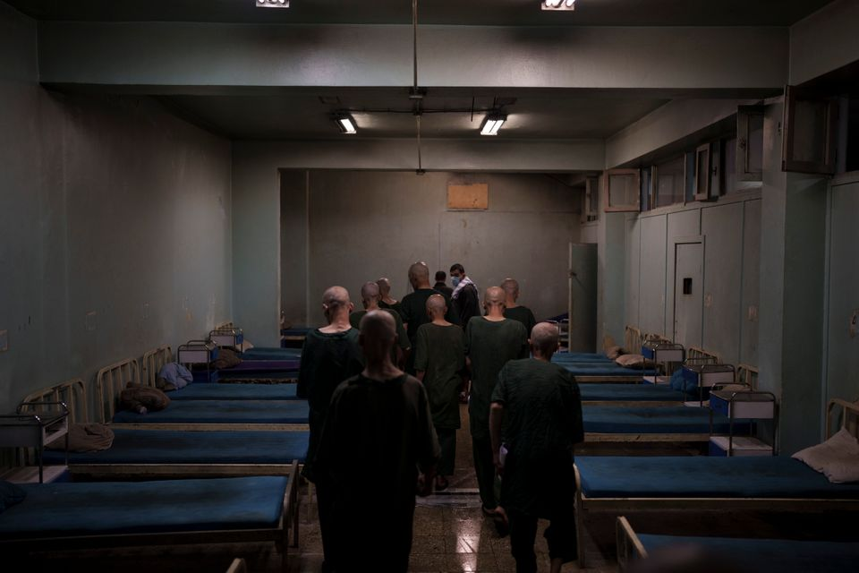 Drug users detained during a Taliban raid are taken to their room at the detoxification ward of the Avicenna...