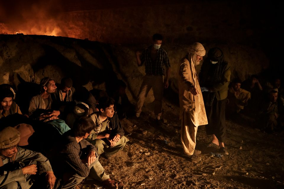 Drug users detained during a Taliban raid wait to be checked at a police station before being transferred...