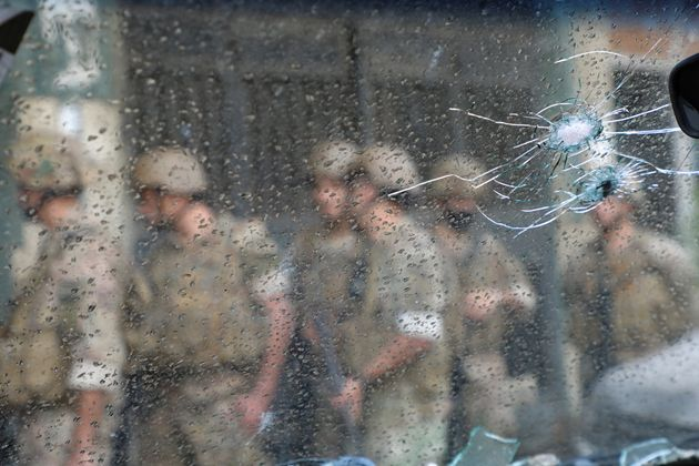 Army soldiers are seen behind a glass with gun holes, after gunfire erupted in Beirut, Lebanon October...